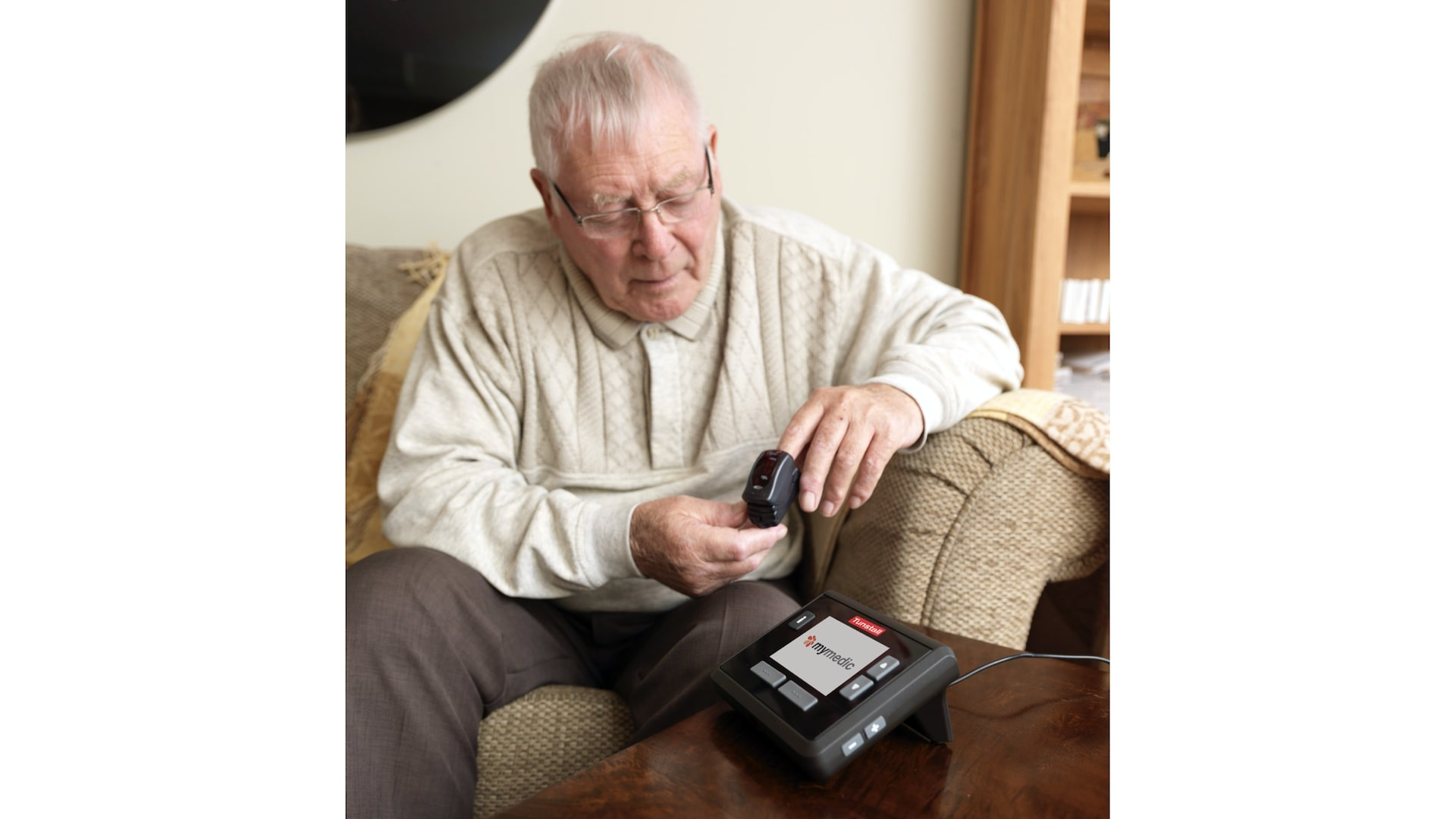 A senior uses a pulse oximeter. He is sitting on a couch at home.