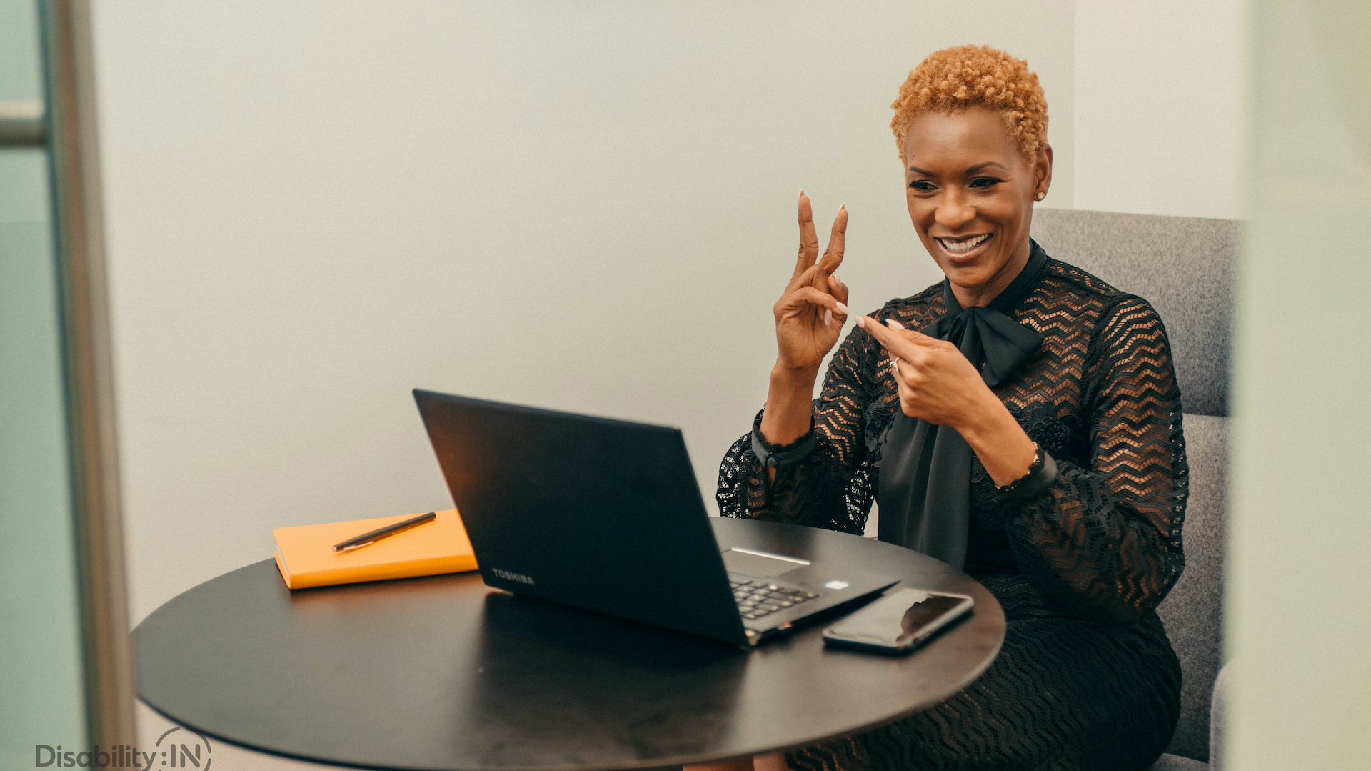 A woman communicates with sign language. She is sitting at a table with a laptop open in front of her.