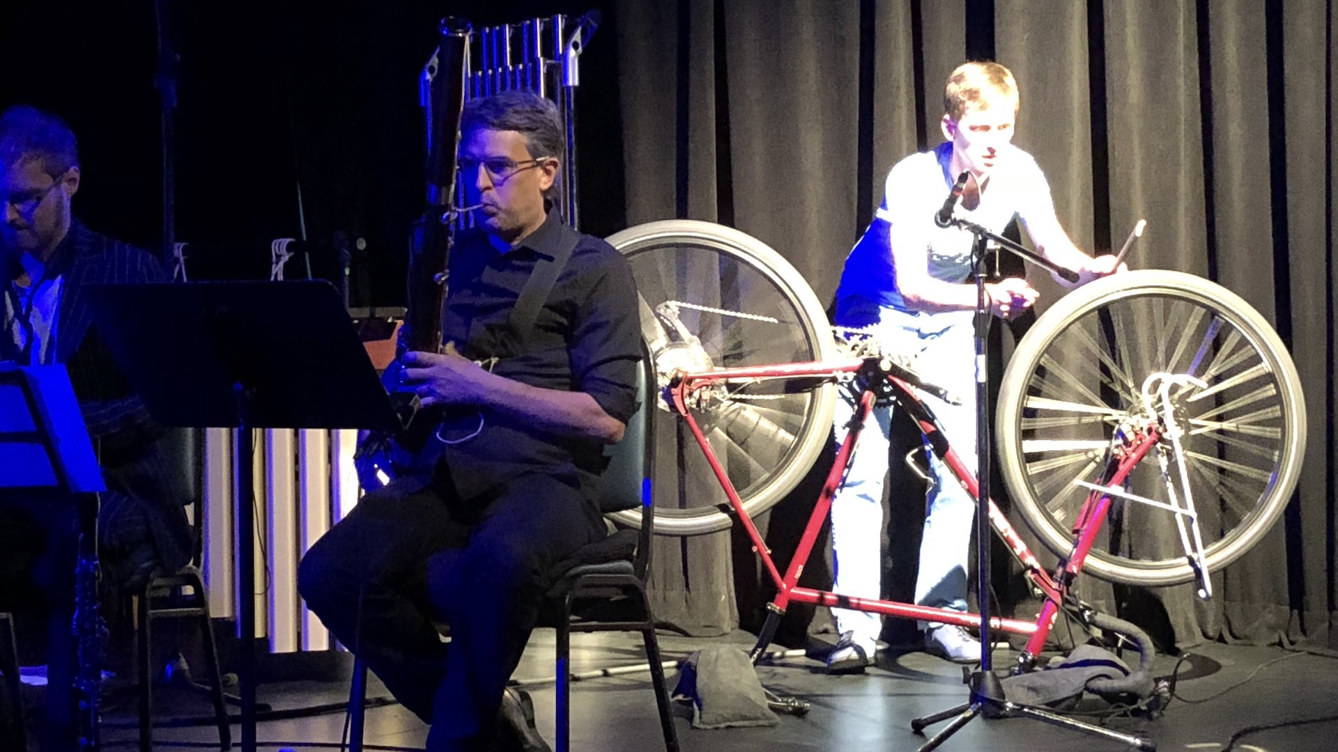 Man sits and plays a musical instrument. Another man stands behind him and makes music using a bicycle tire.