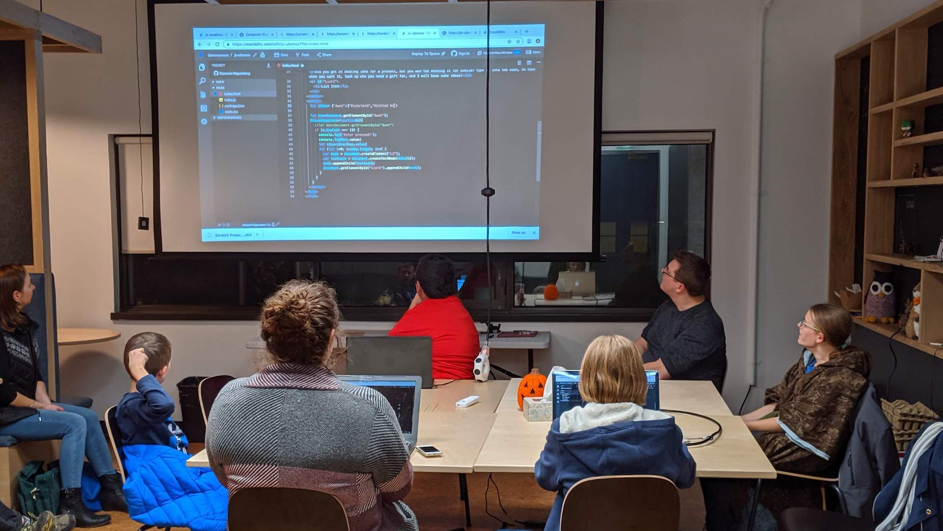 4H members sitting in front of a screen as a leader teaches them web programming basics