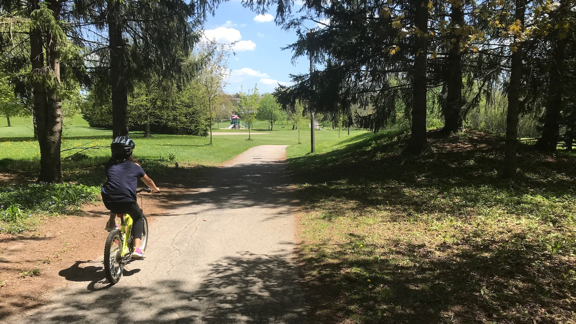 A child rides a bike on a multi use trail in Kitchener, Ontario.