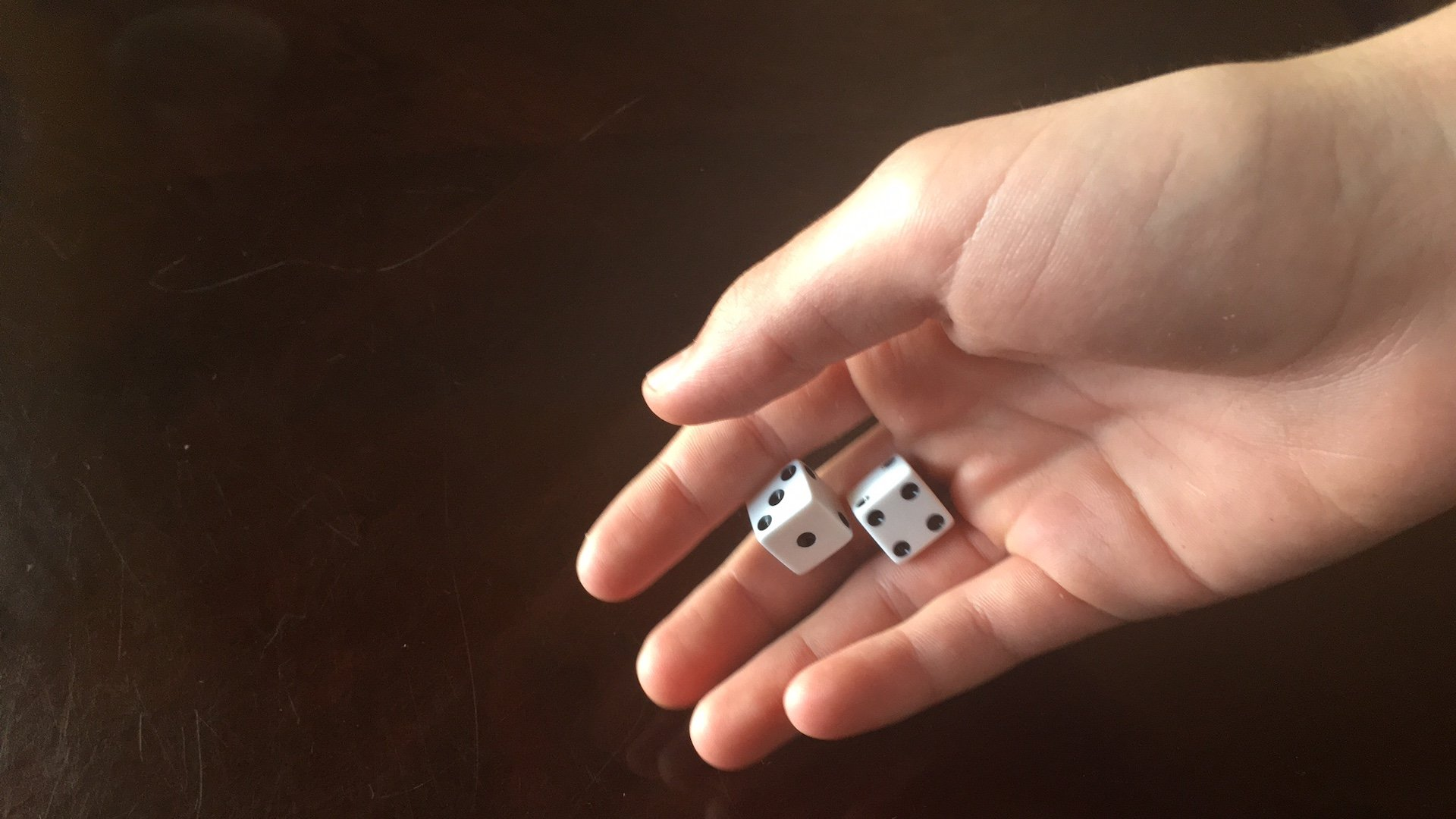 A hand rolling two dice.