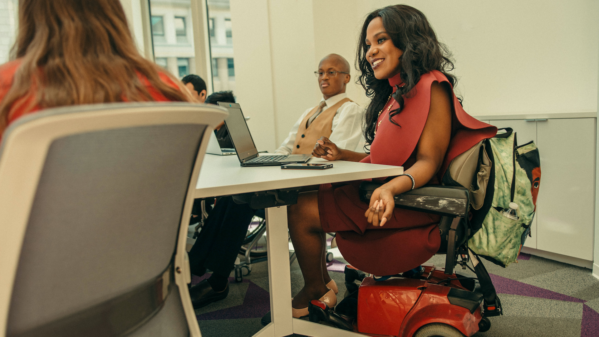 A person in a power wheelchair sits at a meeting table with her laptop open in front of her. She is wearing a red dress and has long dark hair.