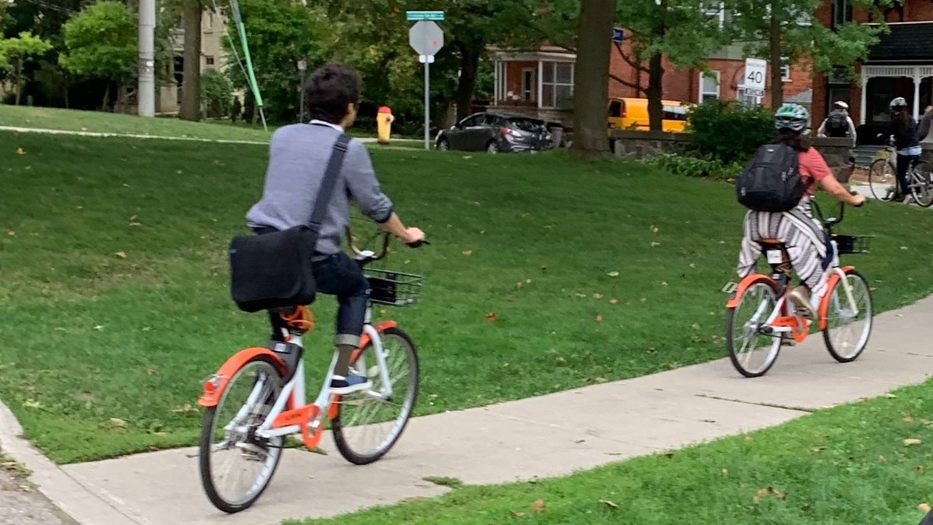 Two people ride Drop Mobility bikes along a sidewalk