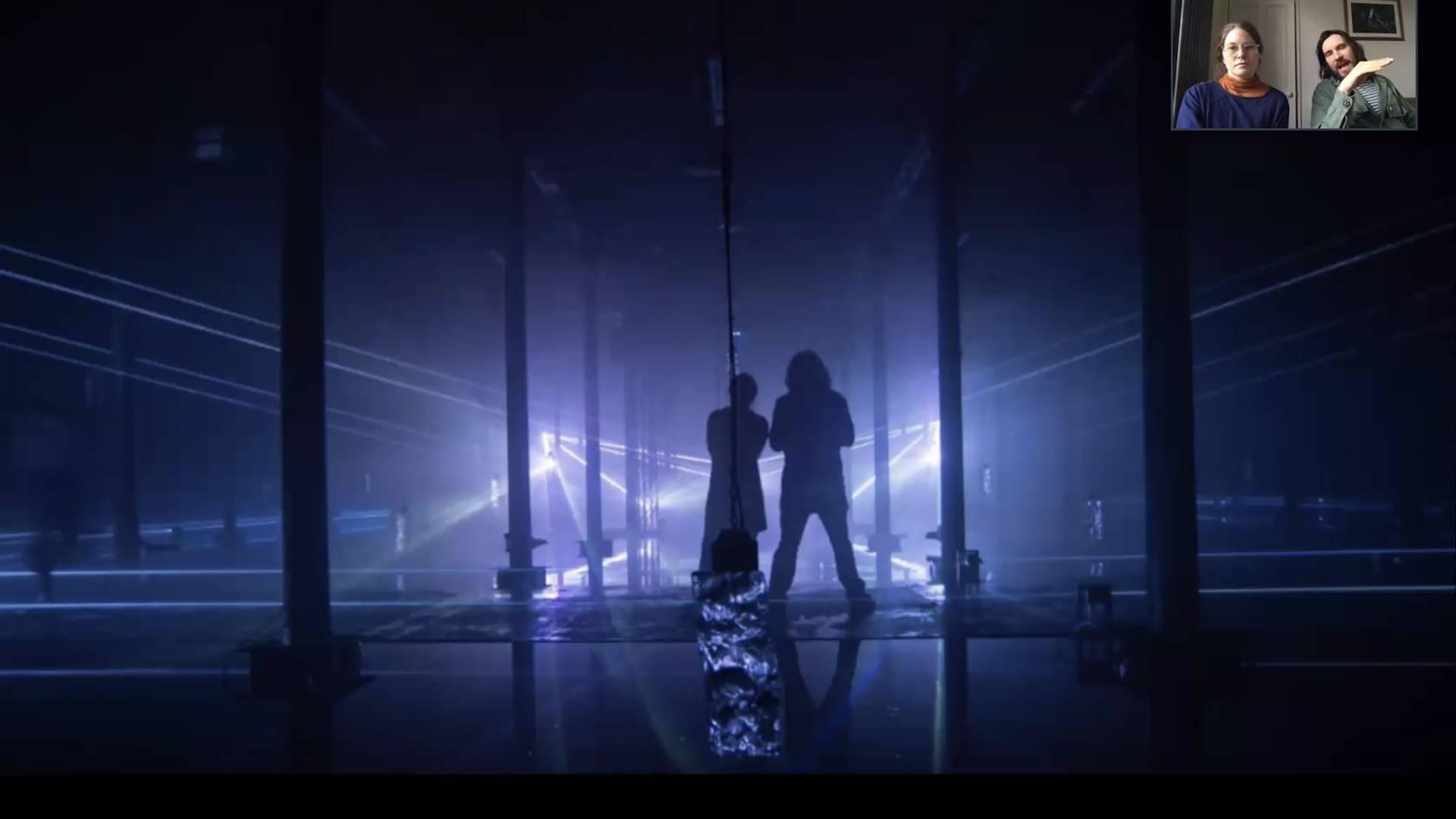 Two silhouettes with purple LED light beams around them.