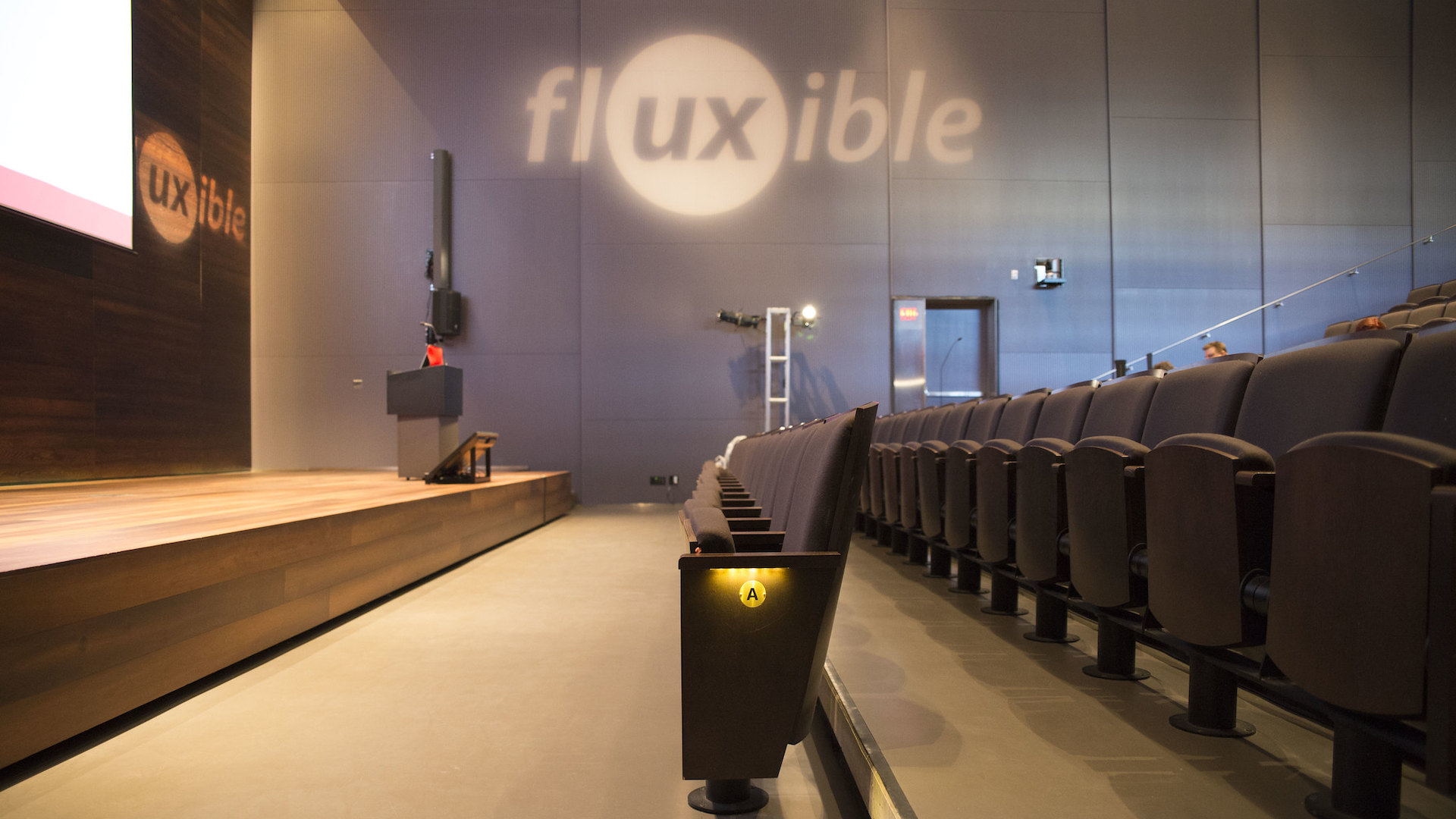 Empty rows of seats in a theatre with the Fluxible logo cast on a grey wall.