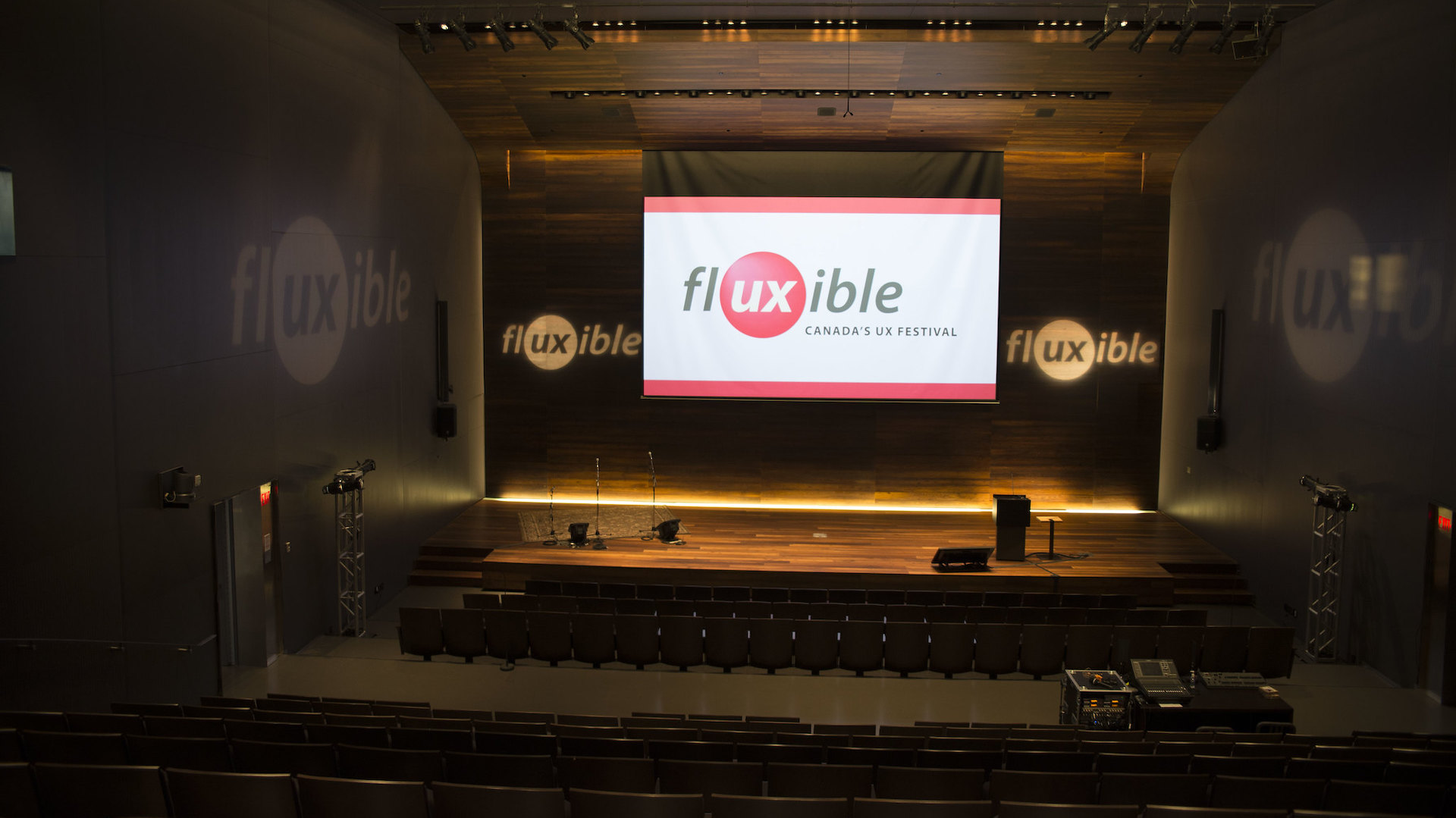The Fluxible logo on a screen on above the stage in an empty theatre.