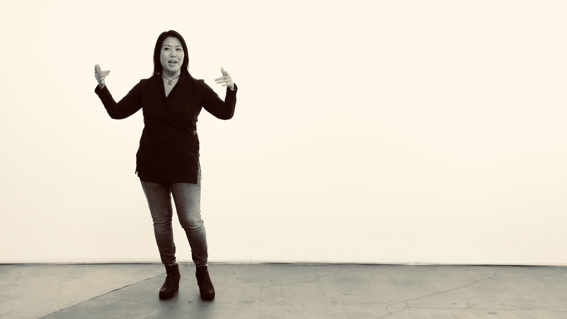Kelly Goto stands in front of a blank wall.