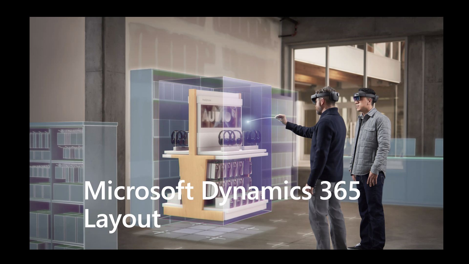 Two people wearing mixed reality headsets, one pointing at a hologram. Microsoft Dynamics 365 Layout written across the bottom.