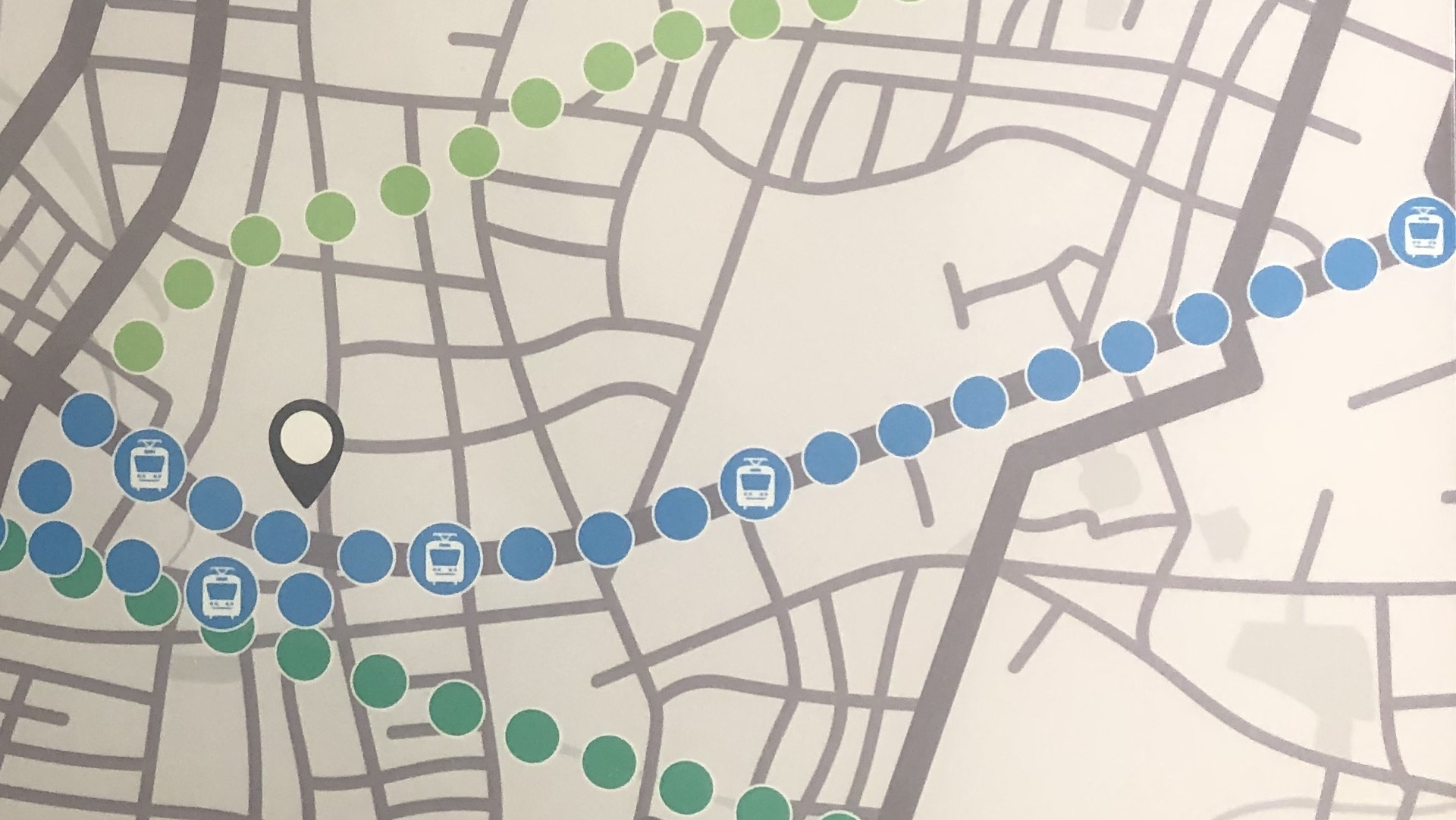 A map with blue, dark green, and light green dots indicating the LRT route, the Spurline Trail, and the Iron Horse Trail in Waterloo Region.