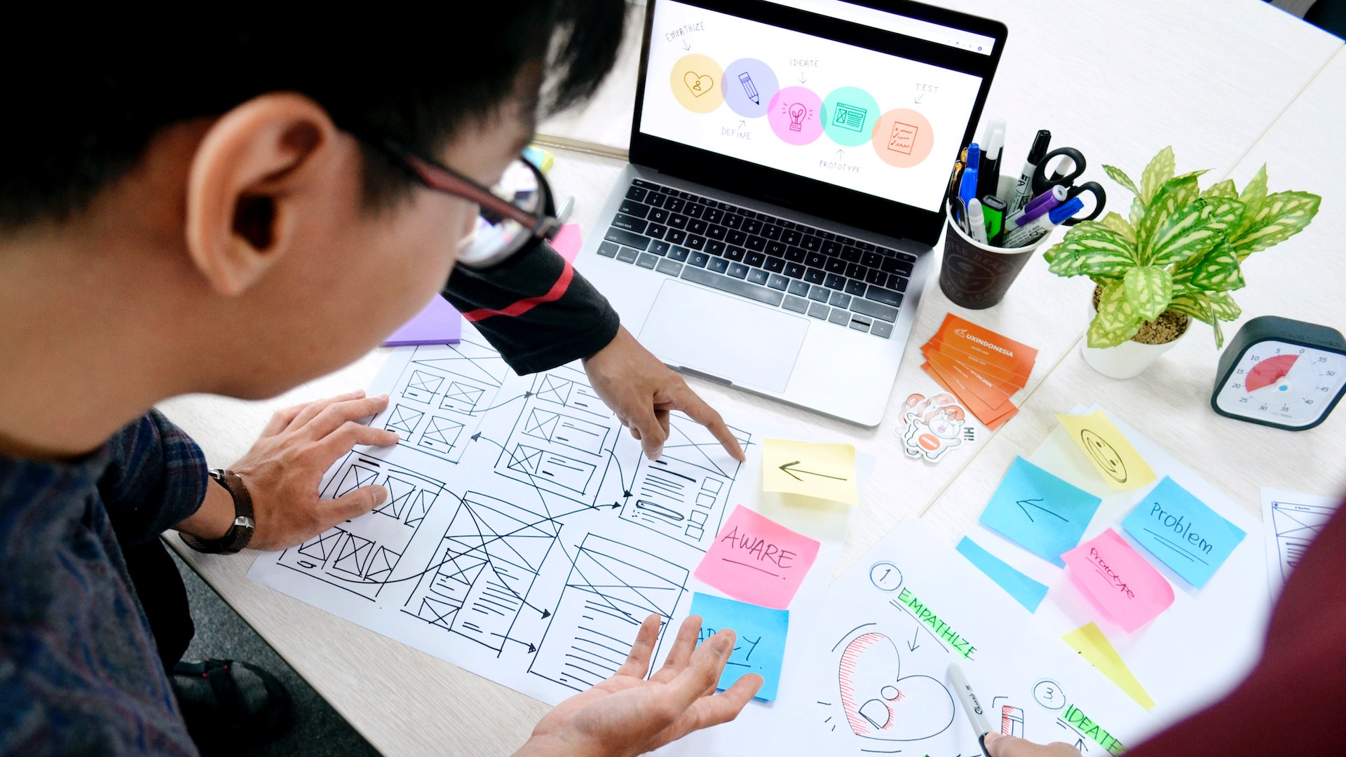 Hands pointing at paper prototypes on a desk. A laptop is open on the table and colourful sticky notes surround it.