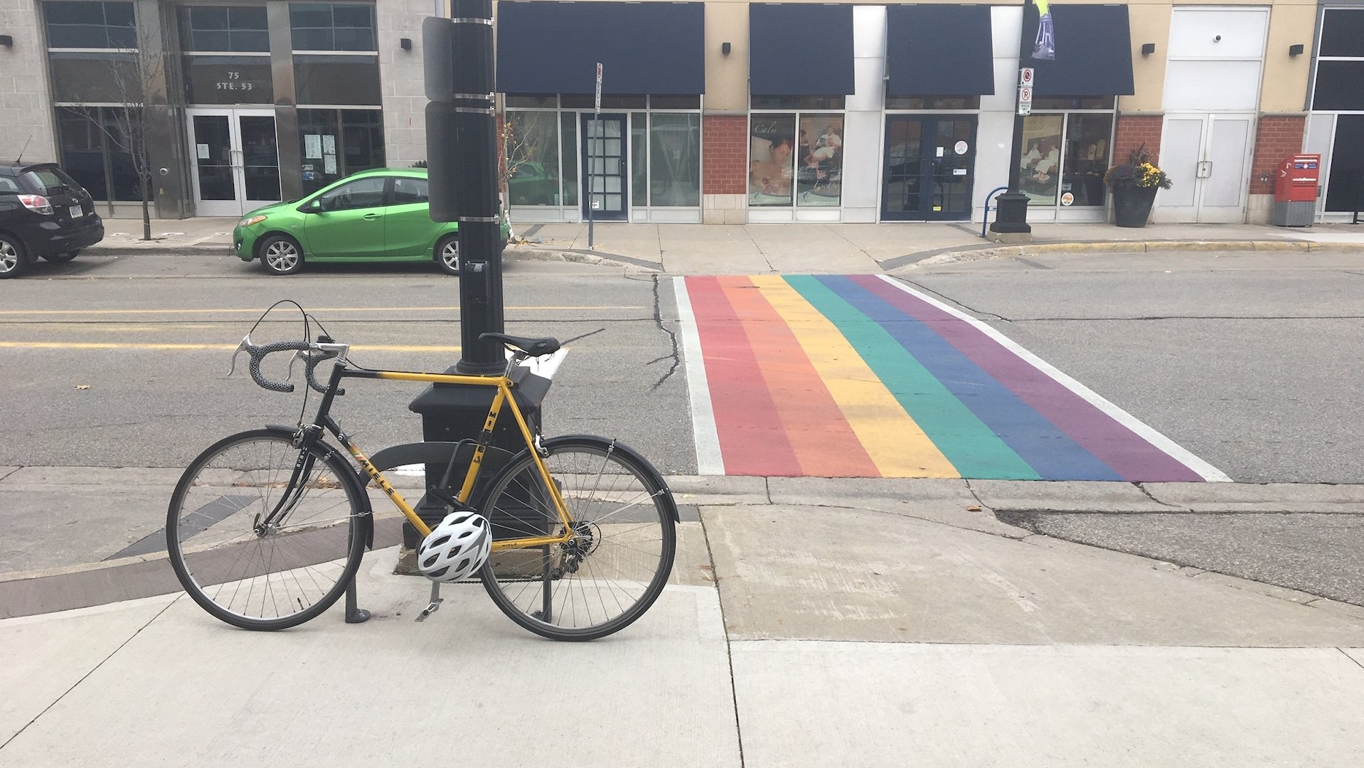 A crosswalk that has painted in rainbow colours. A bike is in the foreground locked to a bike rack with a helmet attached to the bike