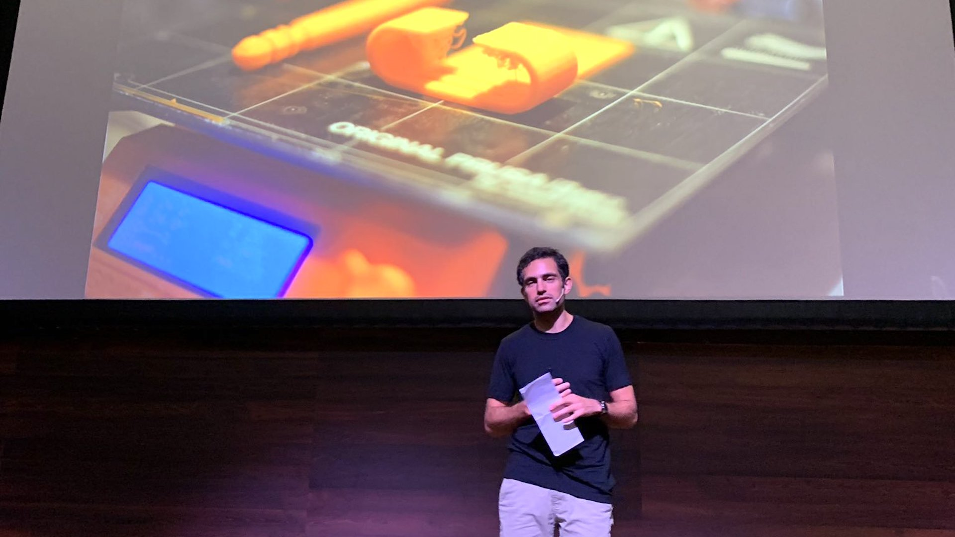 Tarek Loubani on-stage in-front of an image of a 3D Printer he uses to improve battlefield medicine