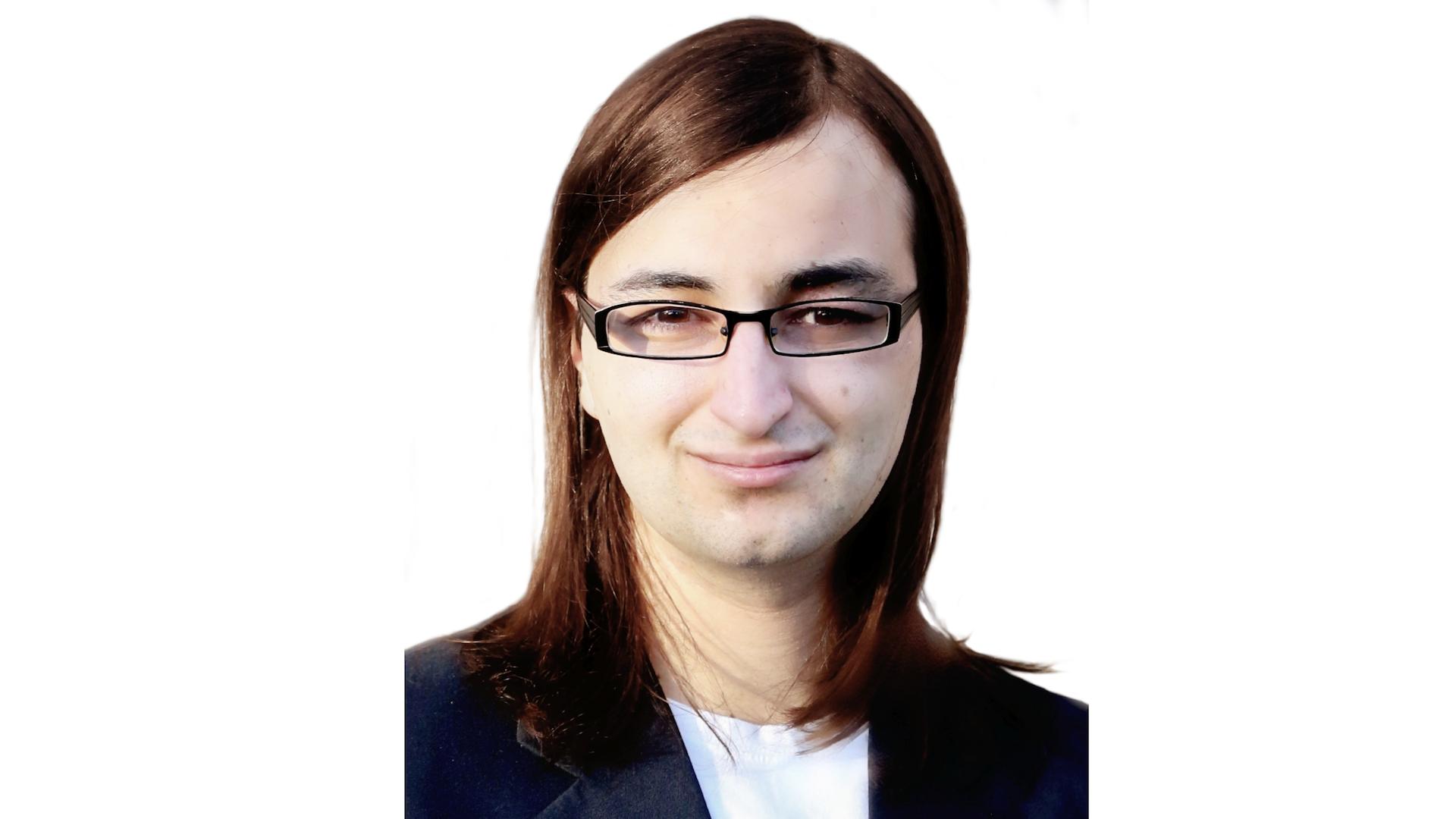 Tyler Delaat wears glasses a white shirt and dark blazer.