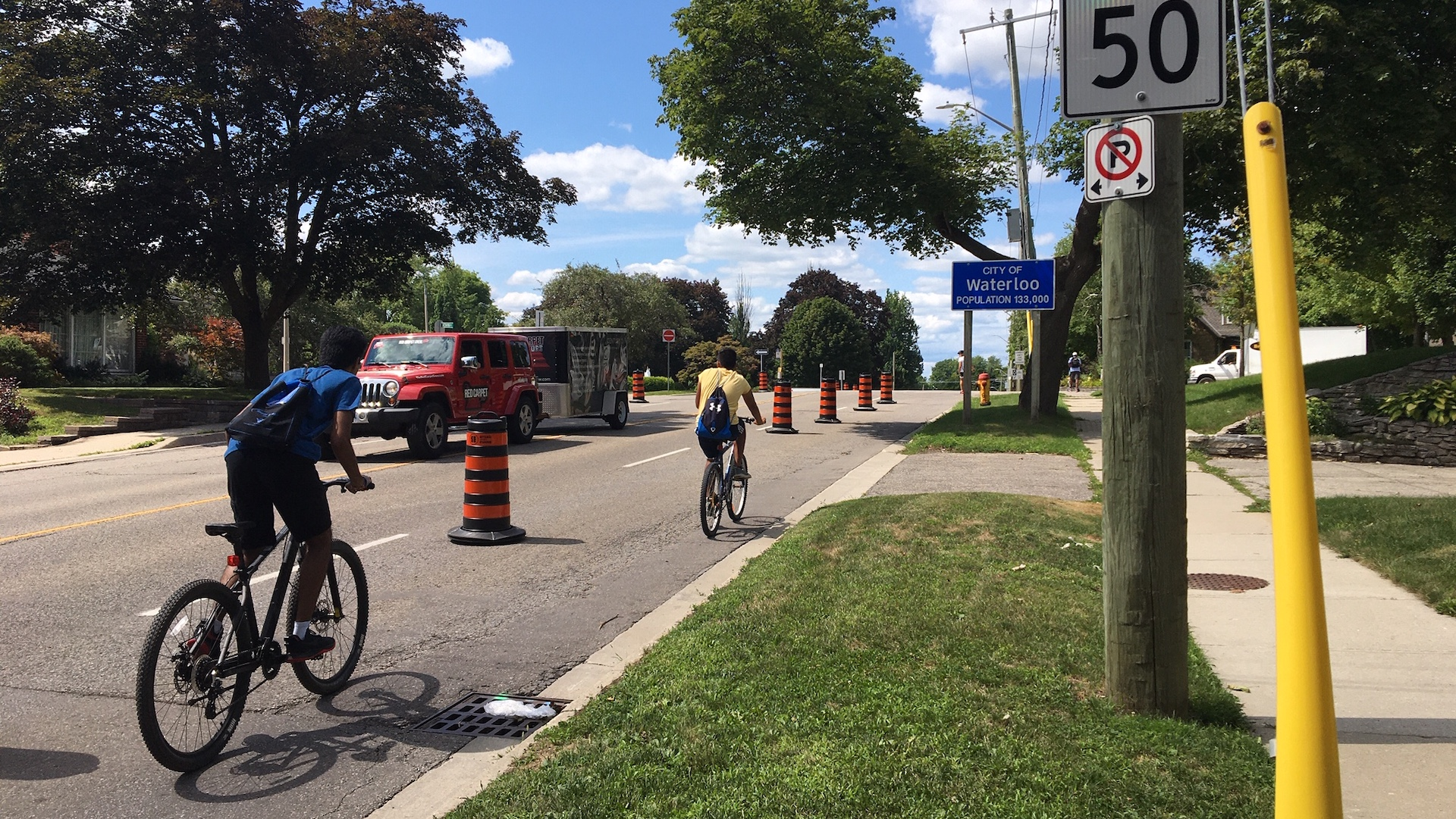 Two cyclists on a road, separated by construction barrels to protect them from traffic in Waterloo, Ontario.