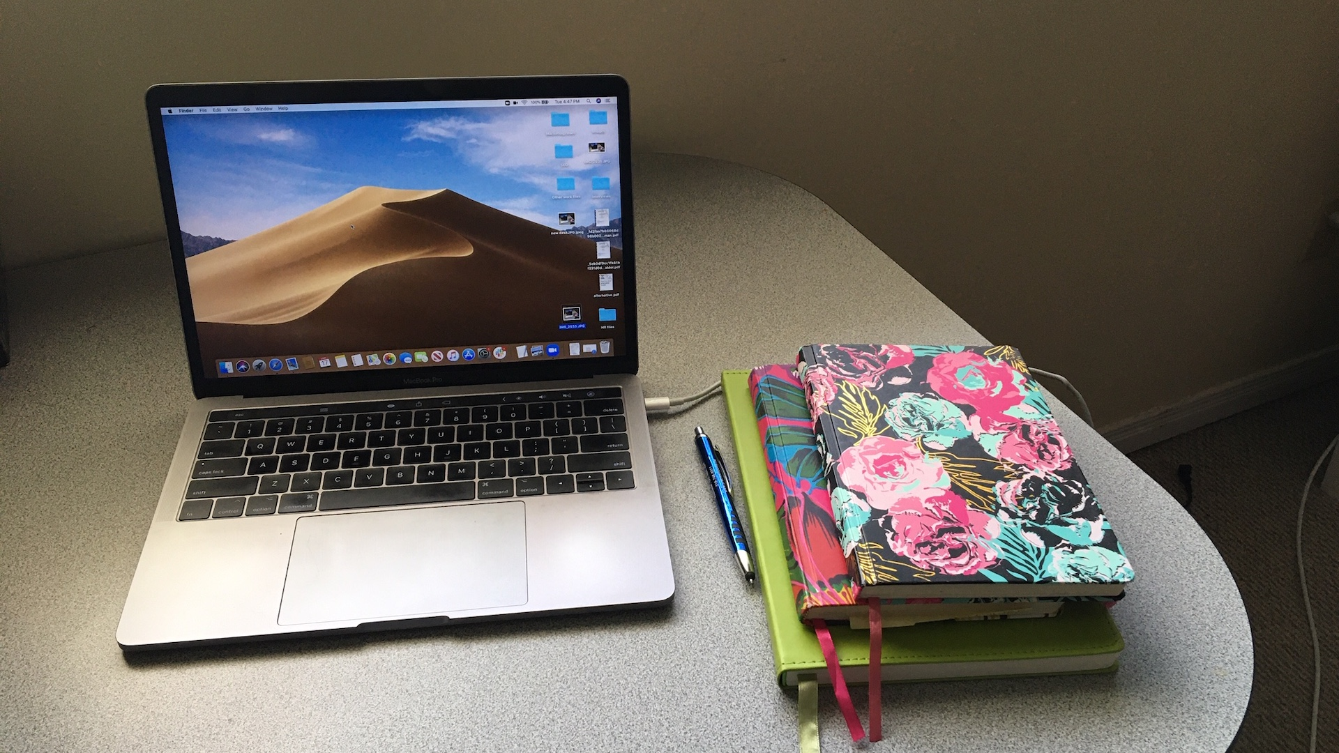 An open laptop on a grey desk with three notebooks stacked next to it.