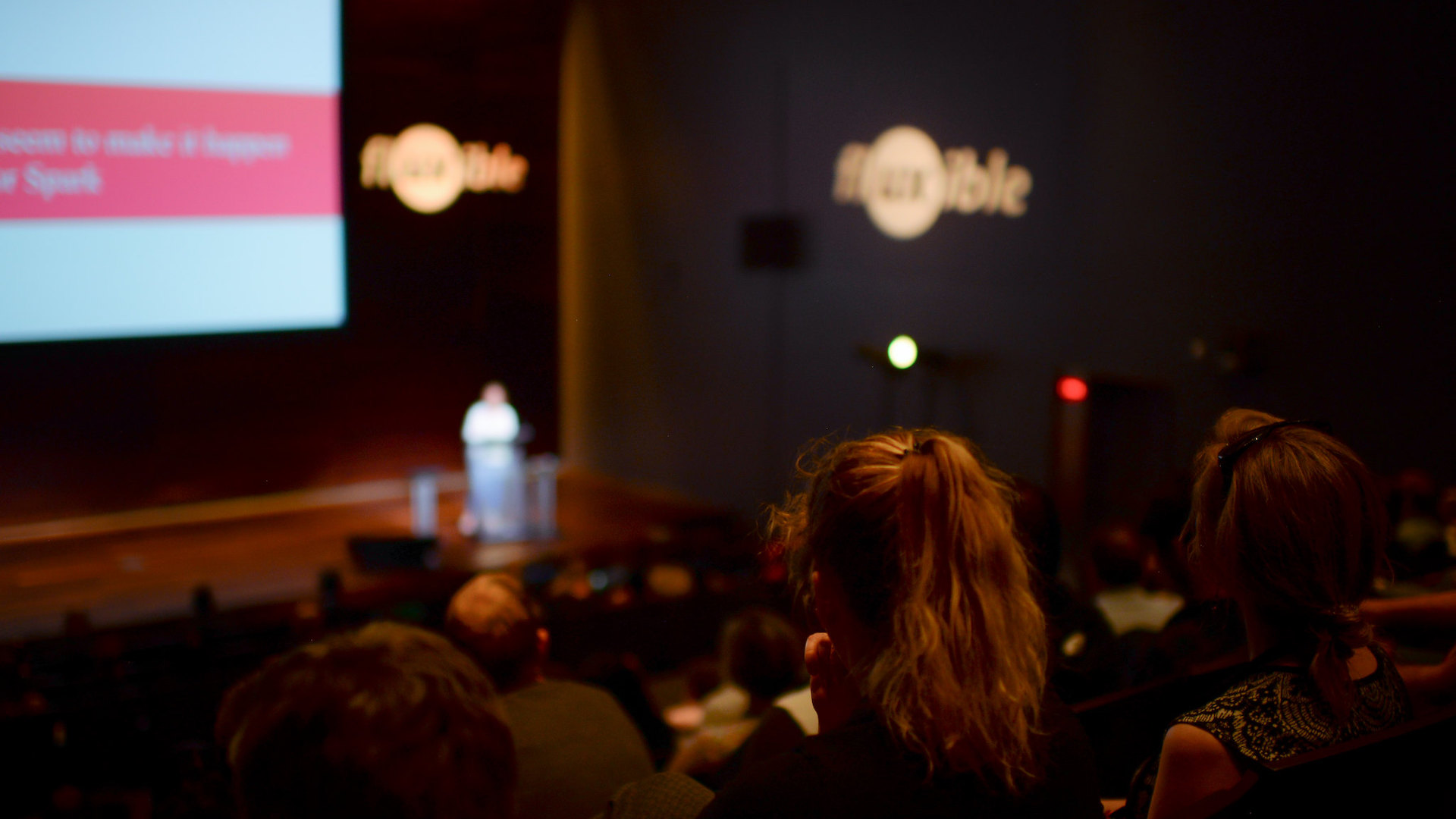 A person stands on the stage during Fluxible Conference while people from the audience look on.