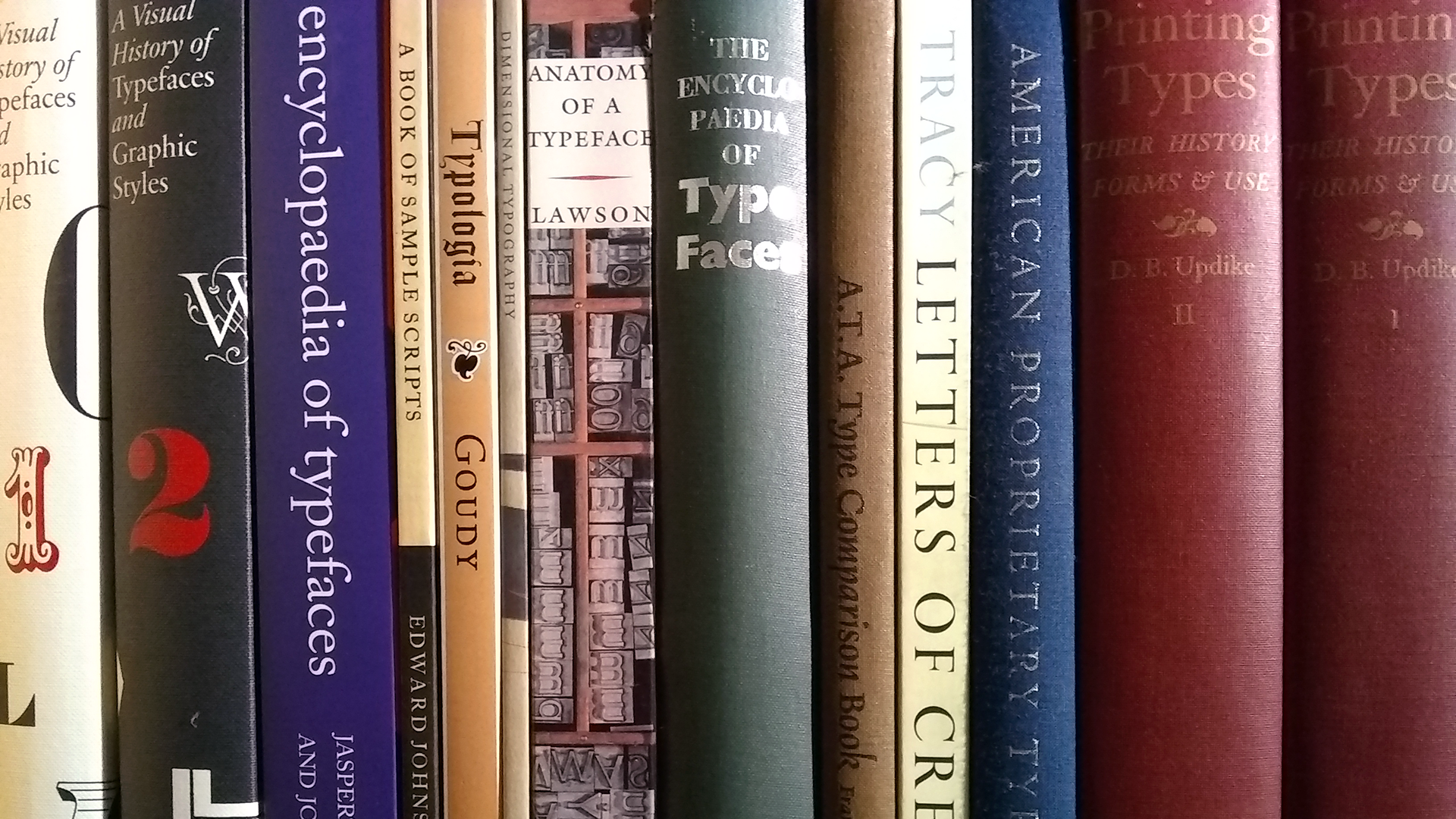 Book spines lined up on a book shelf.