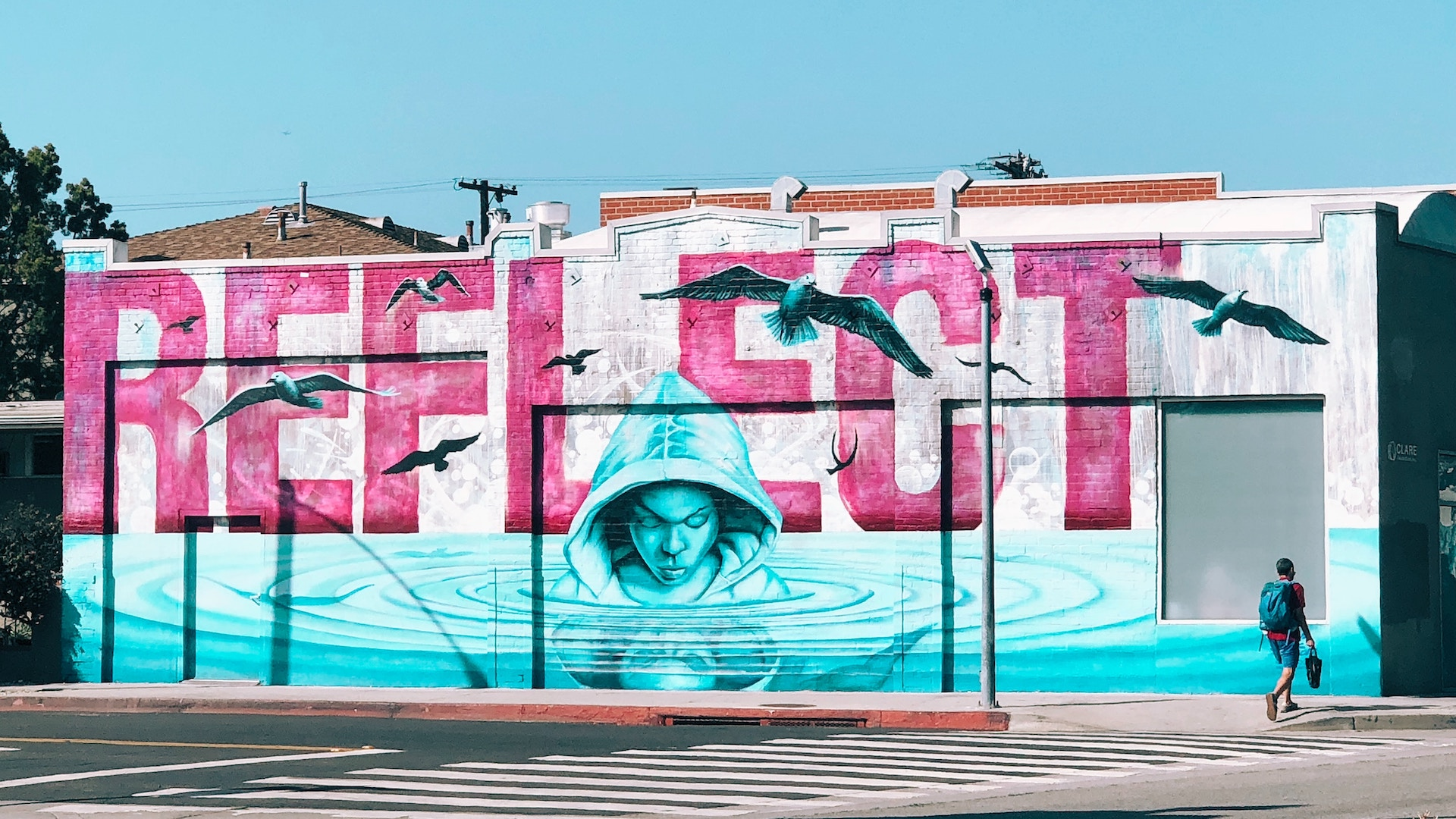 A pink and blue mural on the side of the building that features a person looking into rippling water with the word  'Reflect'