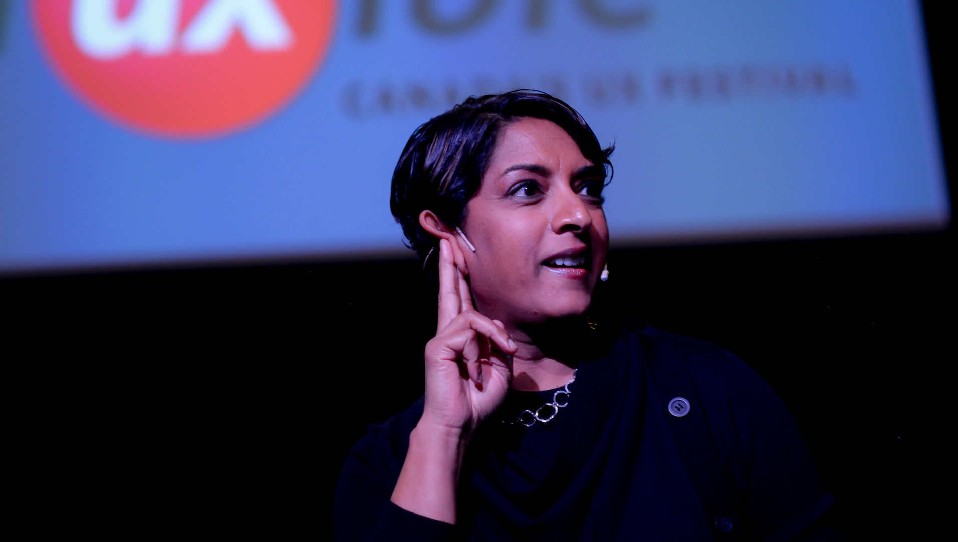 Meena Kothandaraman points up while standing on a stage during Fluxible 2019.