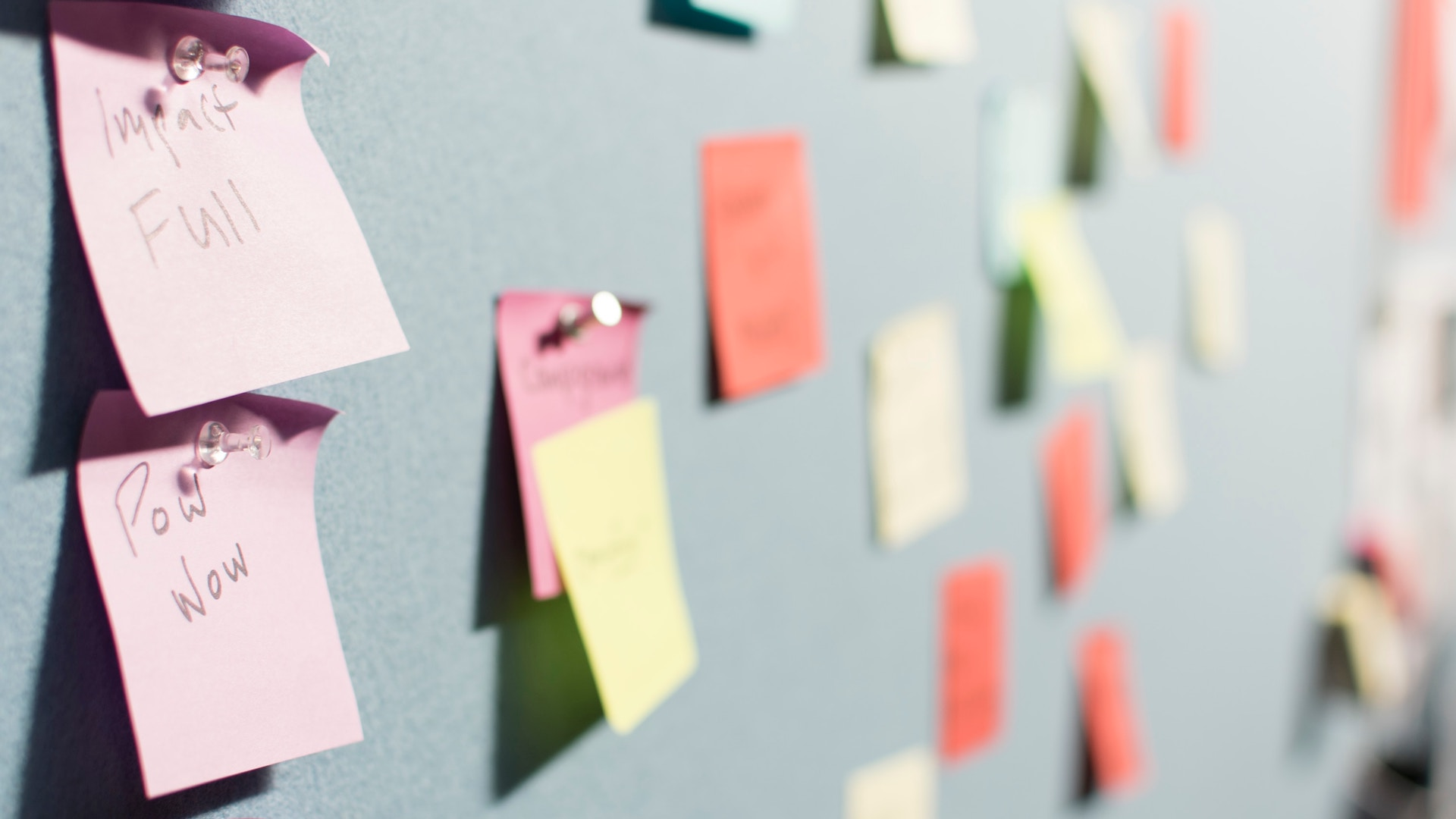 Various colors of Post-it Notes on a wall