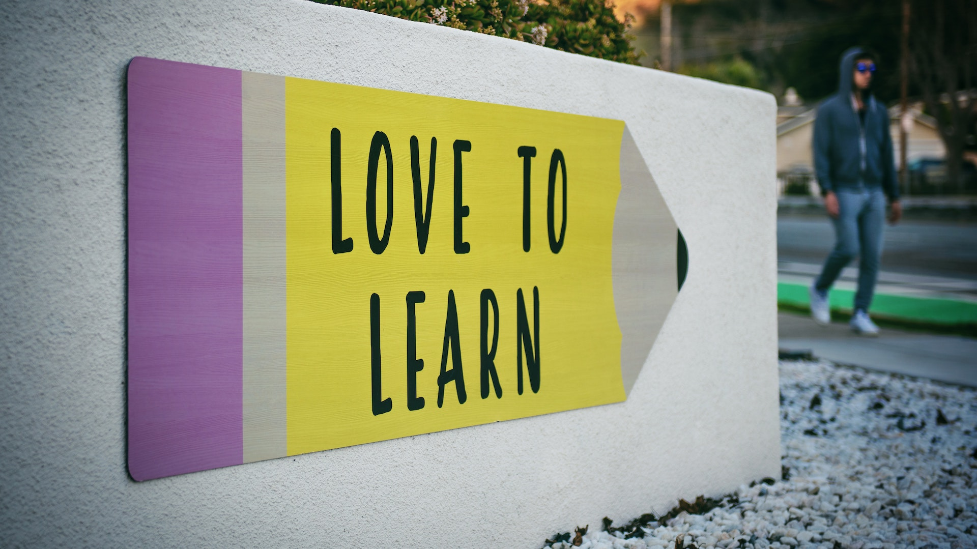 A cartoon pencil that's yellow with a pink eraser. Text on pencil: Love to learn.