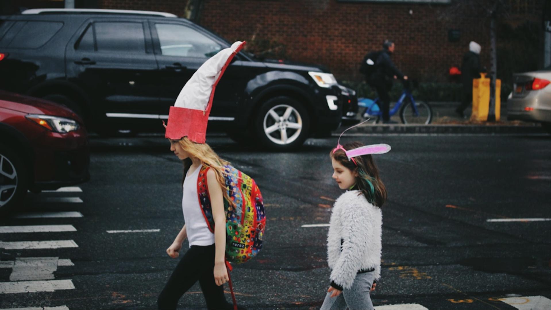 Two girls walking on a sidewalk as a car drives by.